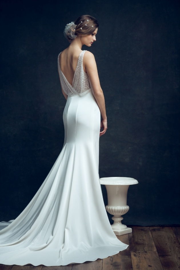 bride with back to camera in elegant dress next to Grecian vase