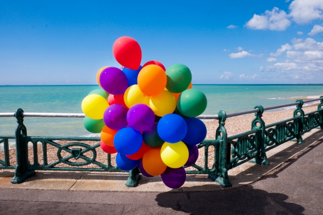 Colourful balloons tied to railings along Brighton seafront beach