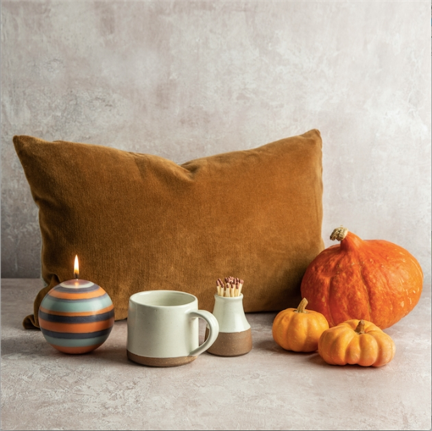 Contents of the Hygge box including a cushion, candle, mug and pumpkins