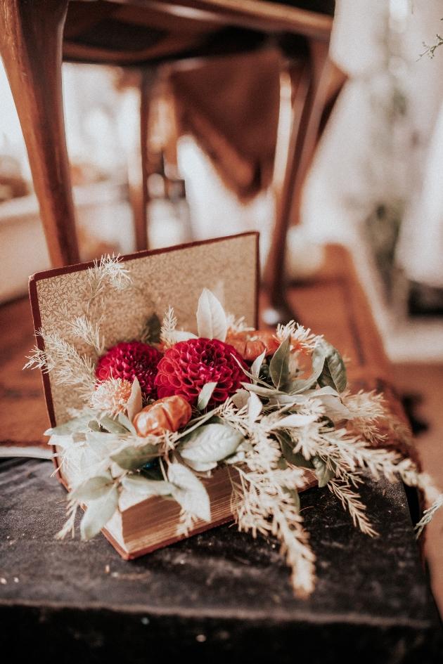 Autumnal flower arrangement featuring red dahlias sitting inside a book