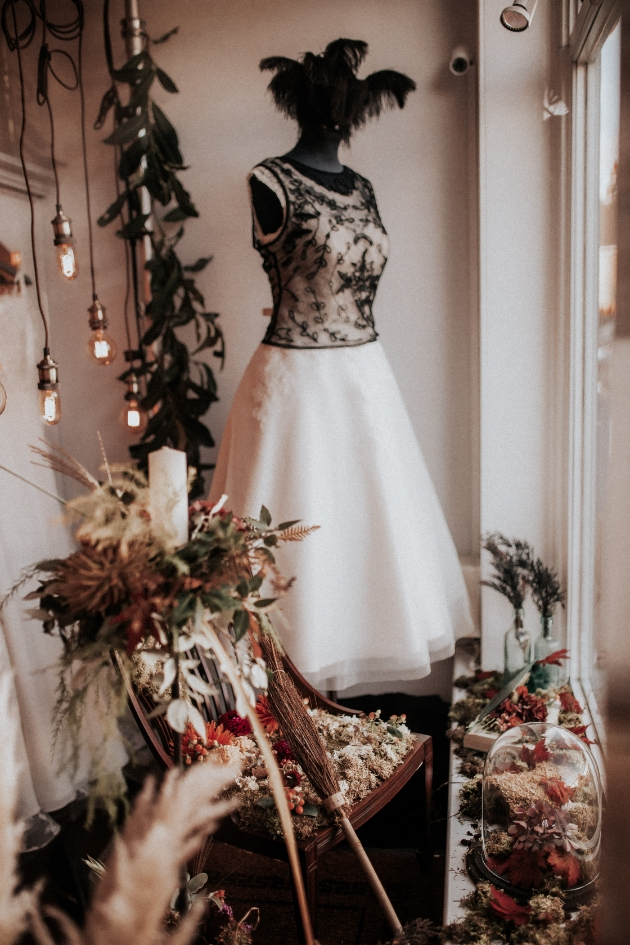 Window display of The Bride Shop with Hallooween autumnal display and black lace detail dress