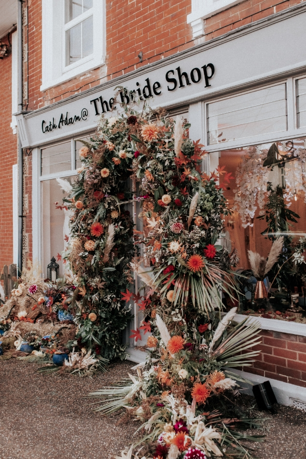 Flower arch over the entrance of The Bride Shop with Halloween display