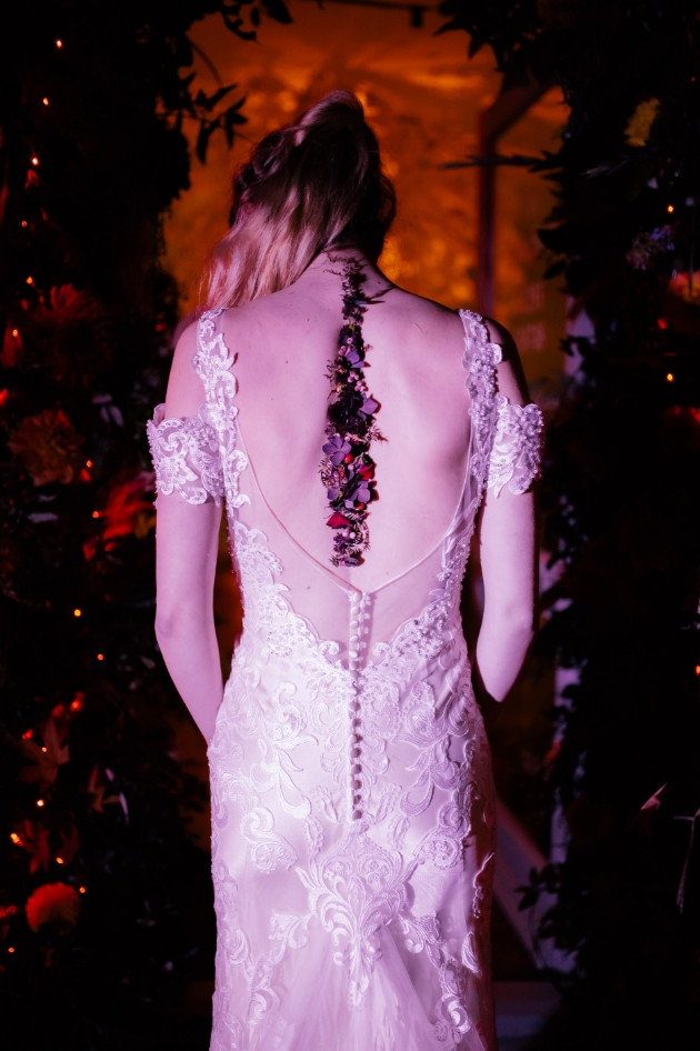 Bride wearing a wedding dress with flowers down her spine