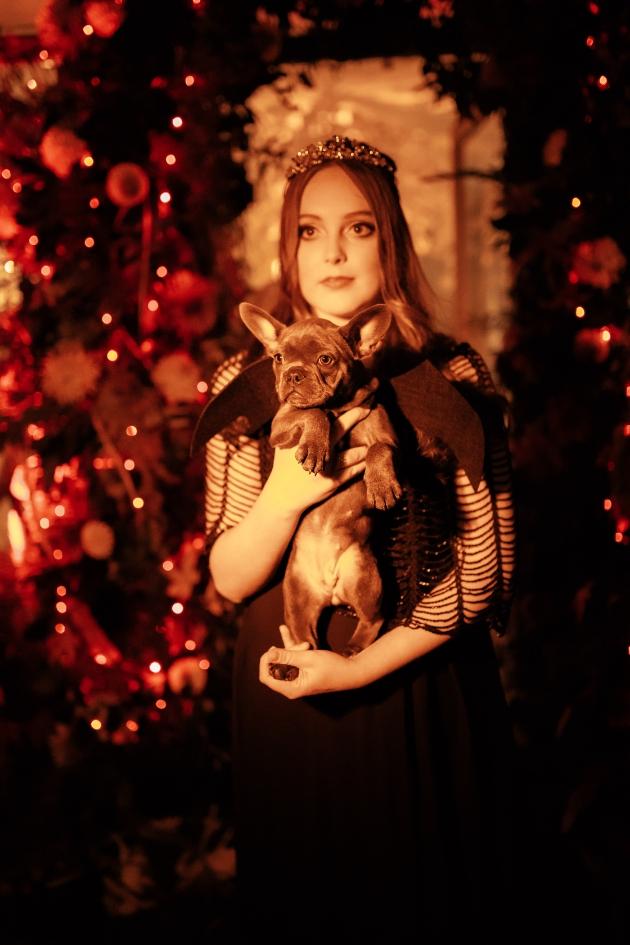 Woman wearing black dress and tiara holding a French Bulldog puppy