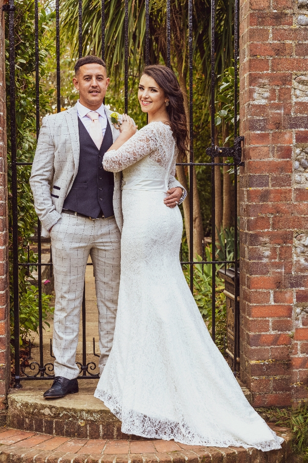 Bride and groom in front of a gate.