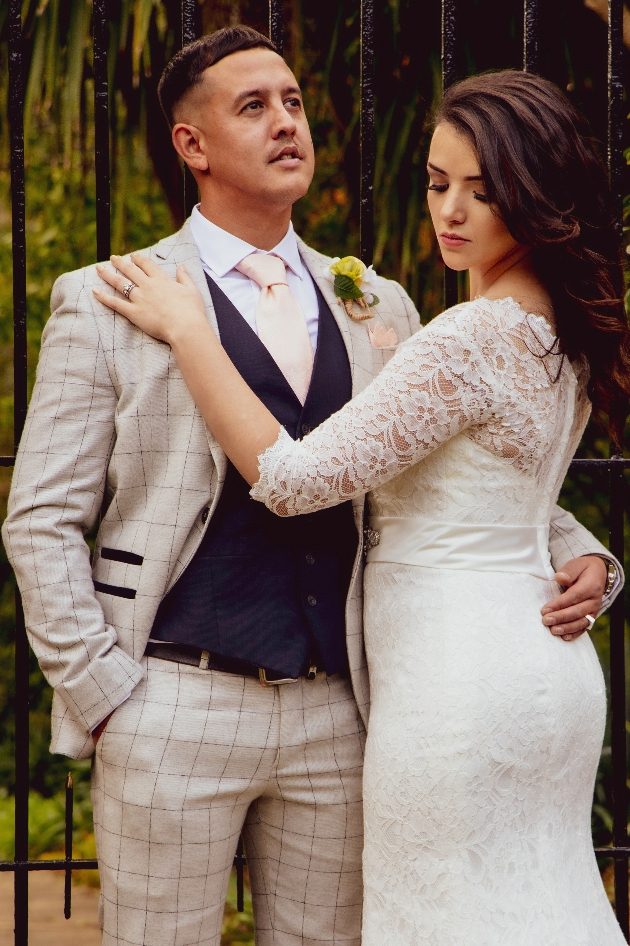 Bride and groom. Groom is dressed in a check suit, navy waistcoat with yellow buttonhole