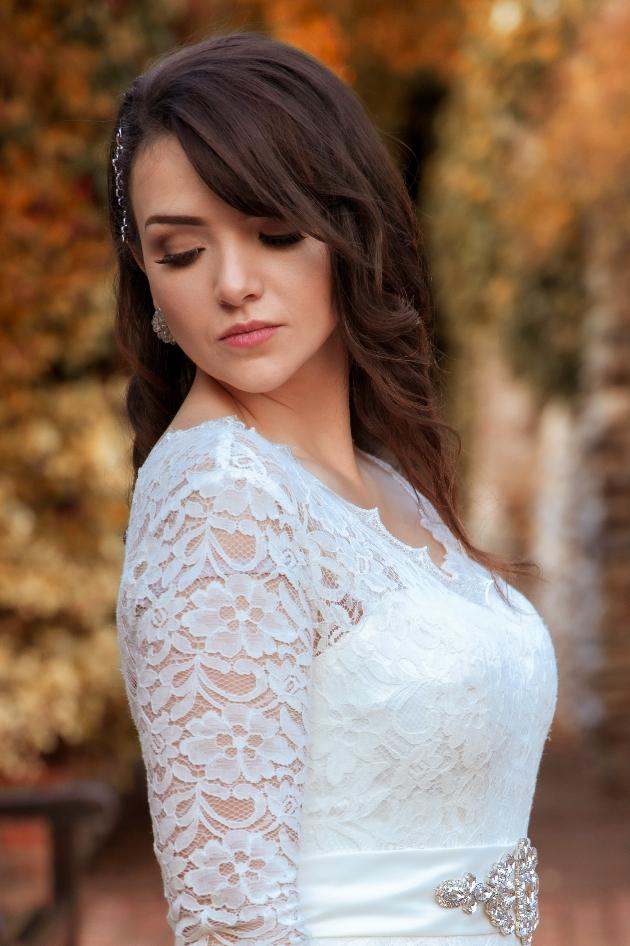 beautiful bride wearing a lace long sleeve dress looking down