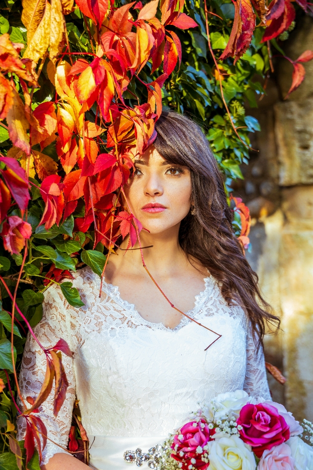 beautiful bride partly obscured by autumn leaves