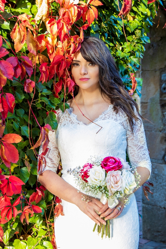 longer shot of bride obscured by autumn leaves holding pink and white bouquet