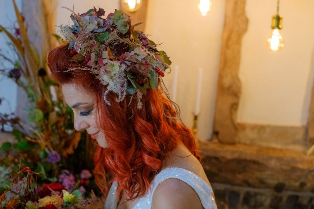 red head bride wearing rustic autumnal flower crown looking down at her bouquet