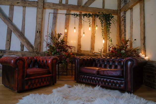 Intimate wedding barn set up with backdrop and brown leather sofas