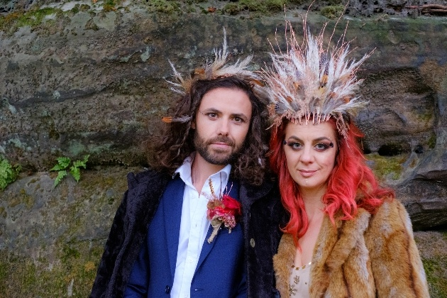 Quirky couple wearing feather head dresses