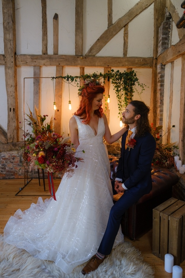 Bride and groom in wedding barn looking at each other bride holds autumnal bouquet