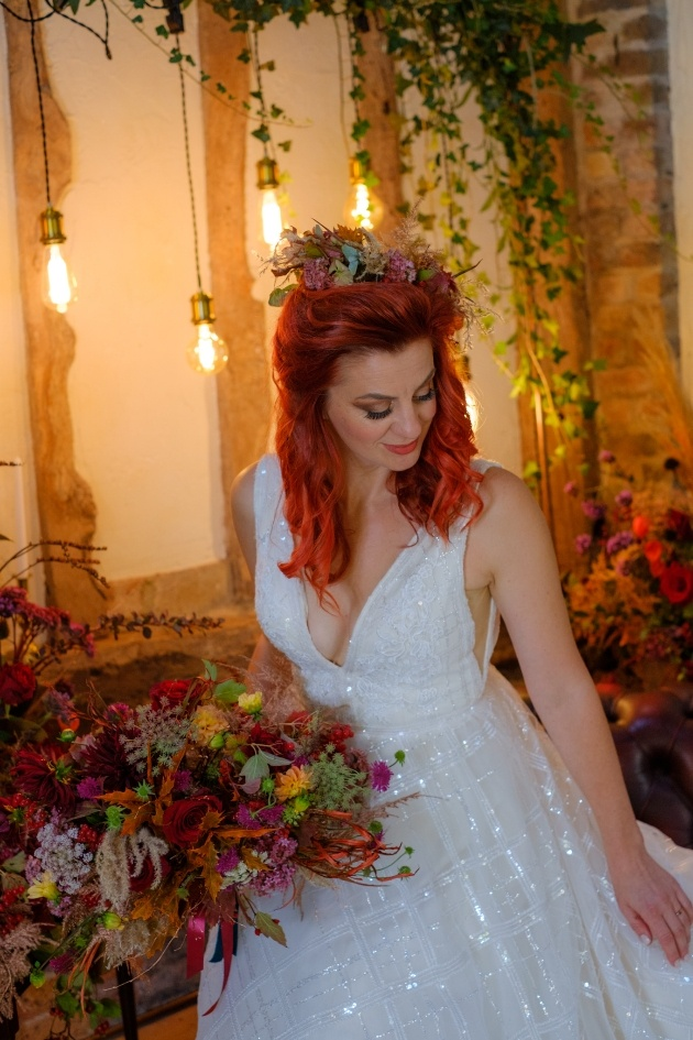 Red headed bride wearing sparkly wedding dress and holding bouquet