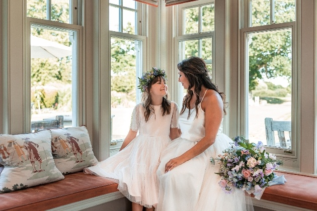 Bride and flowergirl on window seat