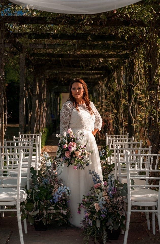bride standing underneath wedding ceremony covered area dressed in english wildflowers