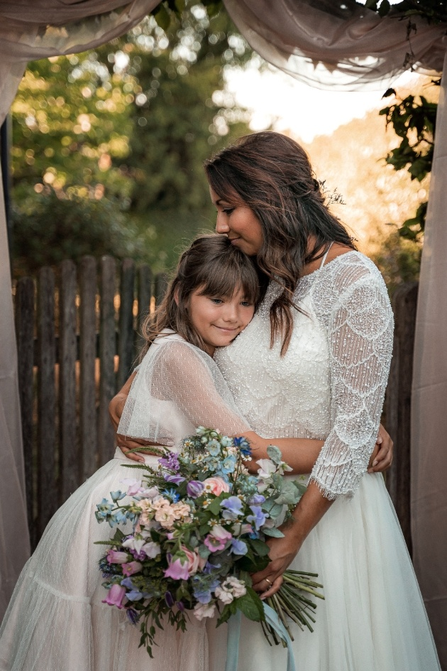 bride holding bouquet and flowergirl, hugging