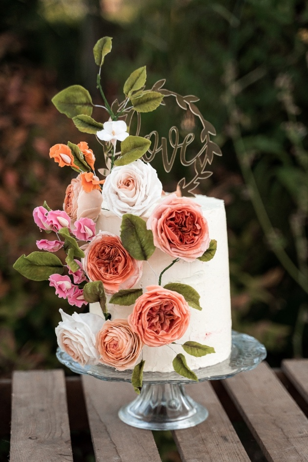 wedding cake with love cake topper, decorated with pink florals
