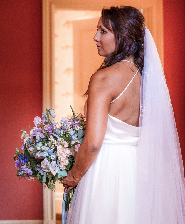 bride wearing a veil and holding a bouquet