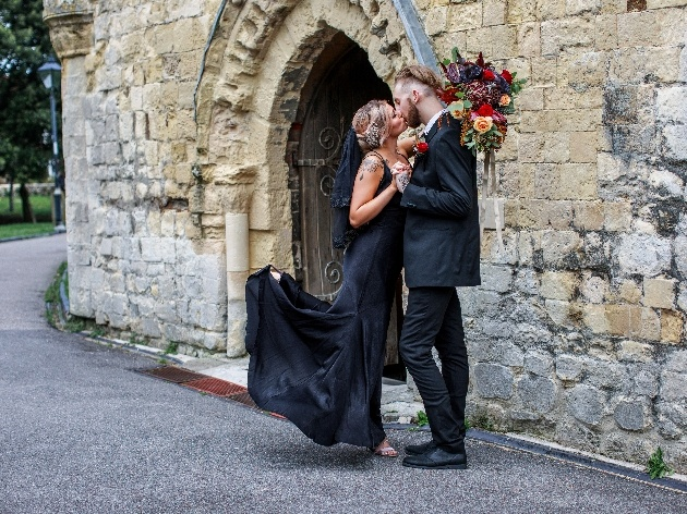 bride and groom dressed in black kissing outside of church