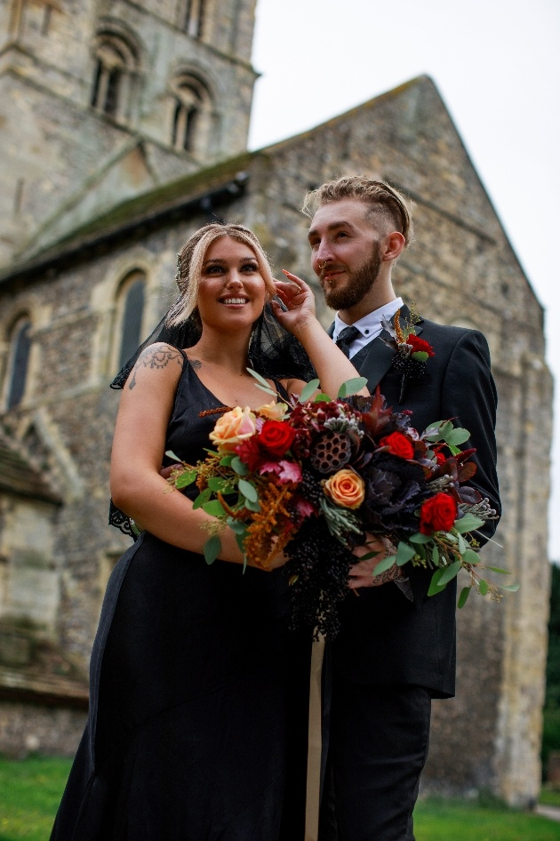 bride and groom dressed in black, outside church, bride holds beautiful red and peach bouquet