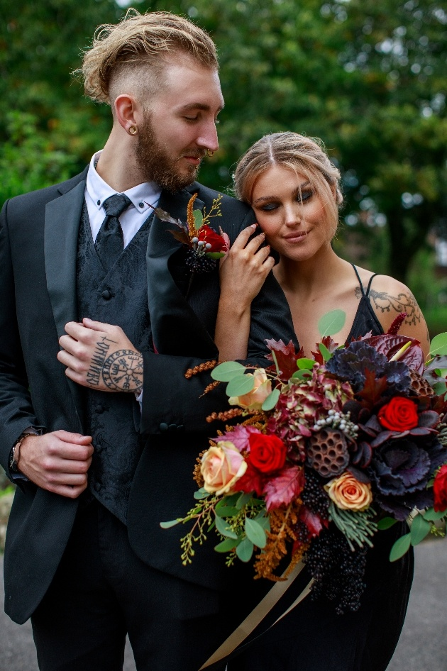 bride and groom dressed in black stroll arm in arm though churchyard