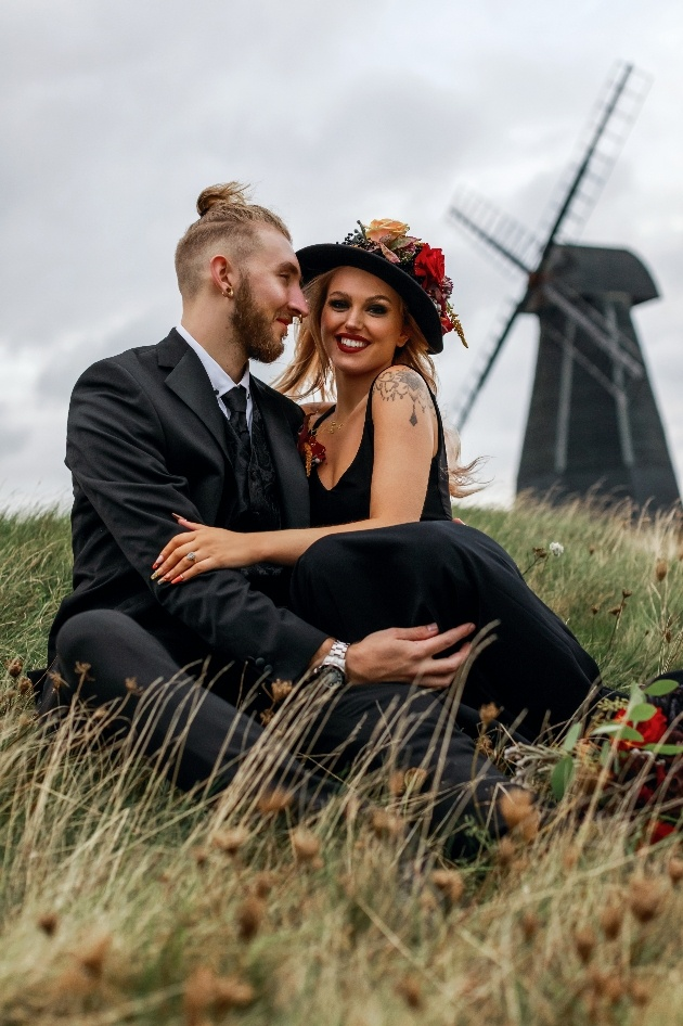 bride and groom sat on the grass in front of windmill
