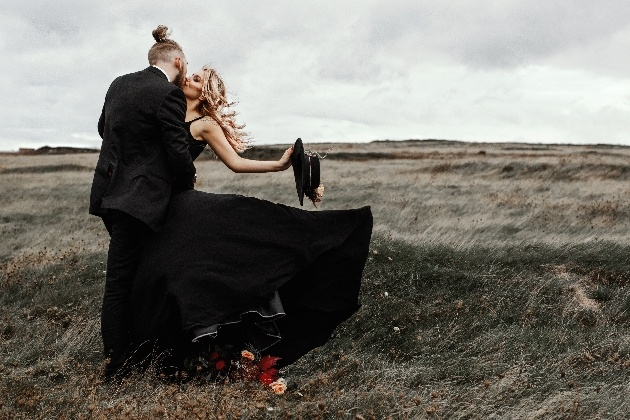 bride and groom dresse in black kissing. Bride's skirt is caught by the wind