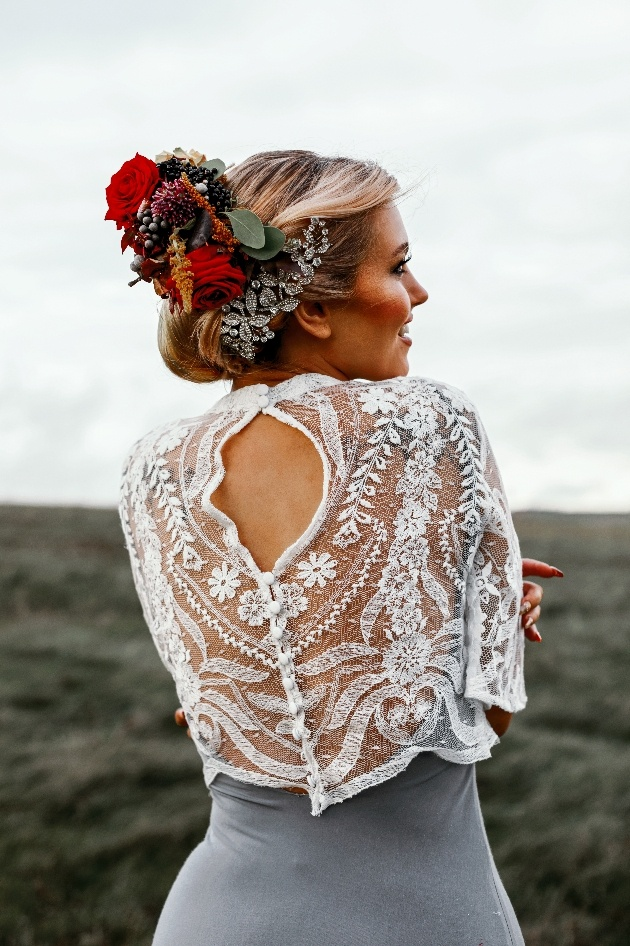 Bride wearing grey and white dress with red floral hair piece