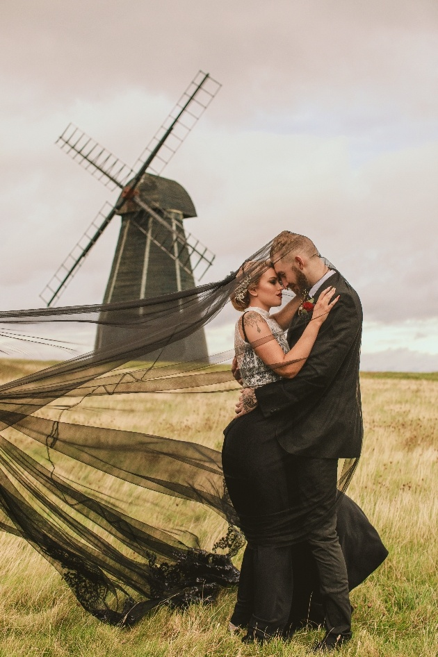 Bride and groom in black in front of windmill. Wind has caught bride's veil which flows out behind her