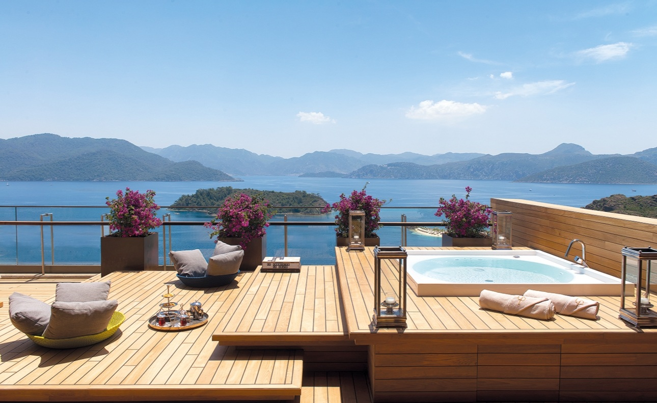 sun drenched terraced with lounger and pool looking out to ocean