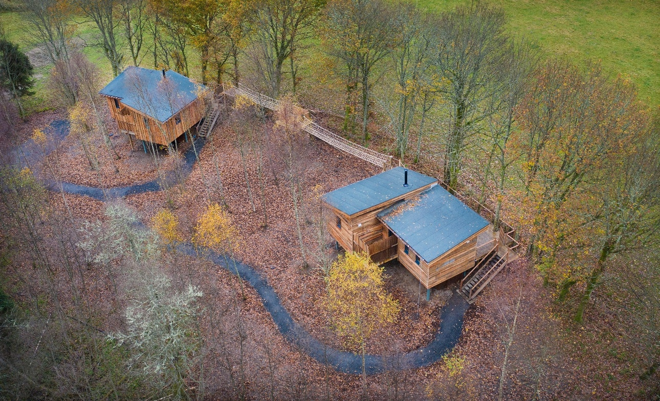 two treehouses low to ground surrounded by trees