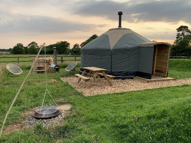 yurt with chimney tables and chairs hot tub and fire pit