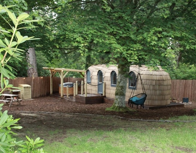 large pod in the woods with hot tub and fire pit