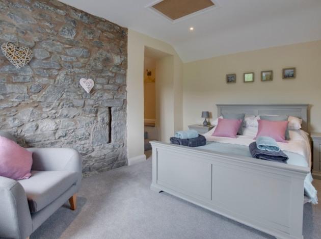 kingsized grey wooden bed armchair in room