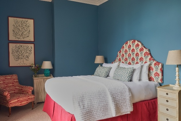 blue room with bed and chitzy decor