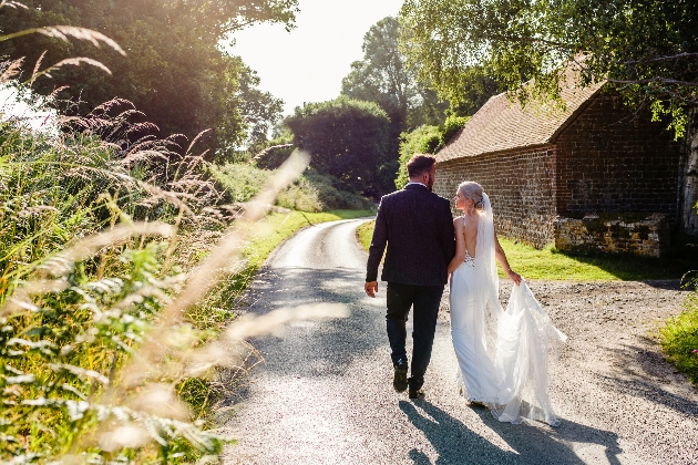 Couple walking down a country lane hand in hand away from us