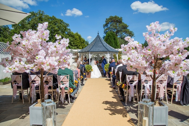 Gazebo wedding with aisle lined with pink blossom trees